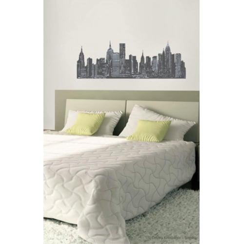 sticker mural dessin de ville collé sur un mur blanc