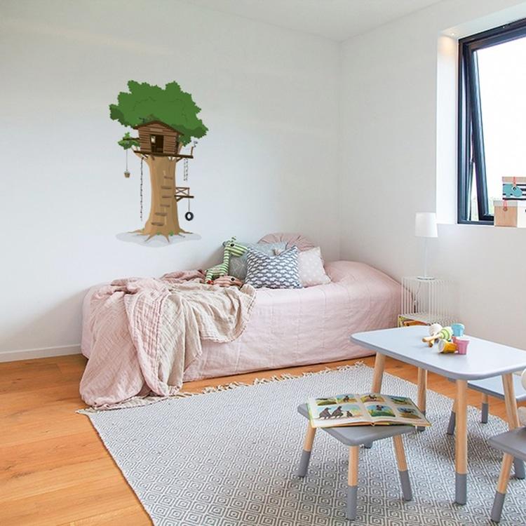 Sticker arbre au-dessus d'un lit rose dans chambre d'enfant