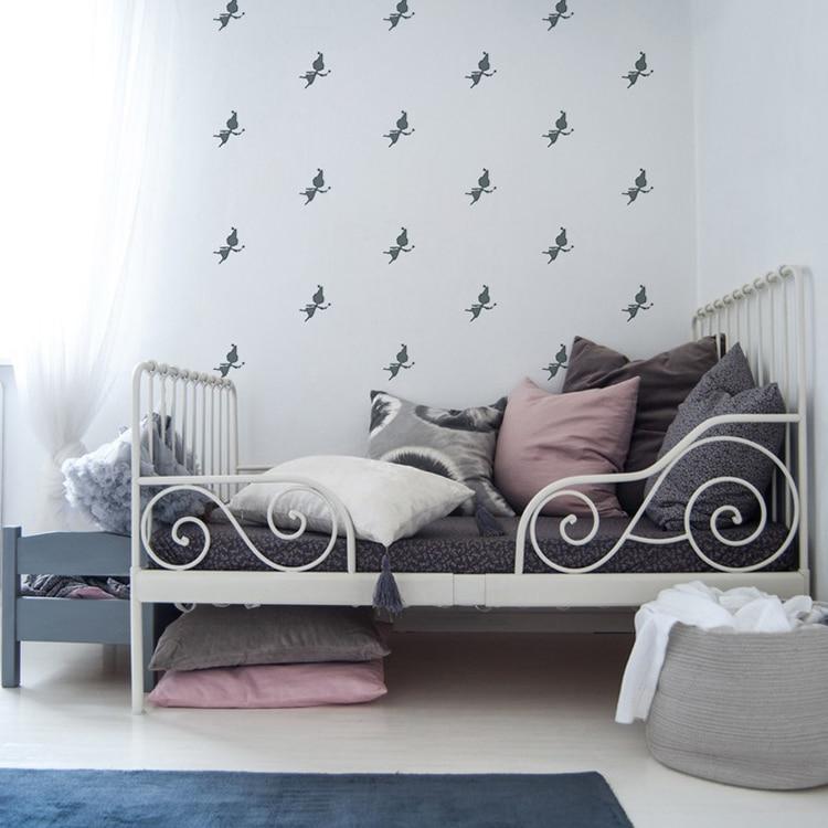 Sticker silhouette fee au-dessus d'un lit gris