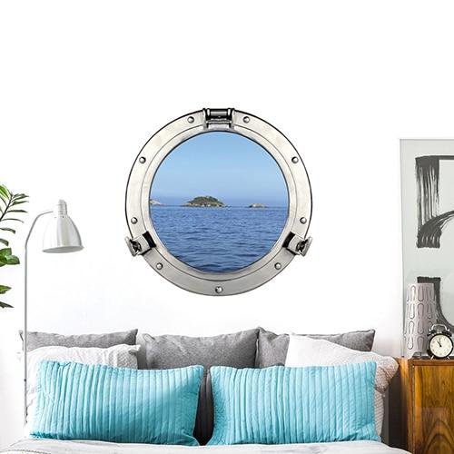 sticker fausse fenêtre hublot de bateau au-dessus d'un lit gris et bleu