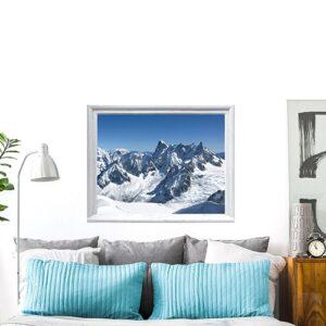 Ambiance déco chalet et montagne dans cette chambre grâce à l'adhésif fausse fenêtre Montagne Enneigées pour déco de tête de lit.