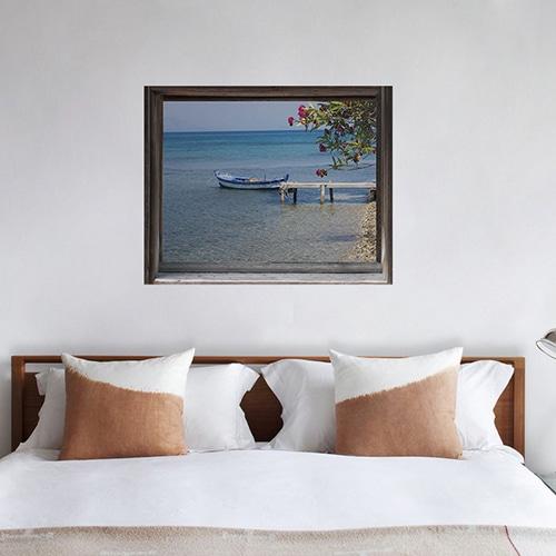 Chambre illumunée par une tête de lit adhésive en trompe-l'oeil comme une fausse fenêtre offrant la vue sur le bord de mer...