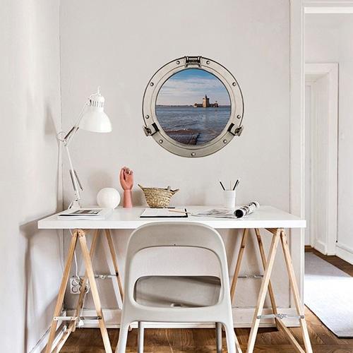 Sticker fenêtre ronde avec vue sur le fort Louvois faux hublot de bateau en trompe-l'oeil au dessus d'un joli bureau blanc.