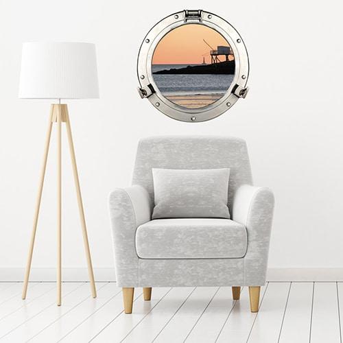 Intérieur scandinave personnalisé avec un hublot de bateau adhésif en trompe-l'oeil représentant une vue sur le port un soir de pêche.