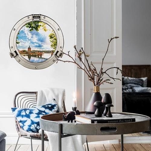 Fenpetre adhésive en trompe-l'oeil représentant un faux hublot de bateau installé dans un salon cosy.