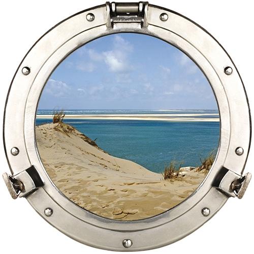 Adhésif mural fenêtre ronde en trompe-l'oeil avec vue sur les Dunes du Pilat et une eau turquoise comme un faux hublot de bateau.