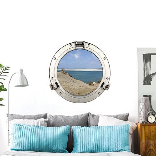 Autocollant mural fenêtre ronde avec vue sur les dunes du pilat et eau turquoise mis en ambiance sur un mur blanc