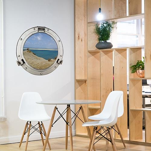 Adhésif mural fenêtre ronde faux hublot de bateau en trompe-l'oeil avec vue sur les dunes du pilat et une eau turquoise dans une salle à manger marine avec un joli claustra de bois.