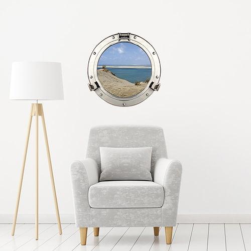 Adhésif déco mural fenêtre ronde en trompe-l'oeil comme un faux hublot de bateau avec vue sur les dunes du pilat dans un intérieur déco sobre et tendance.