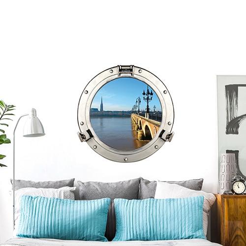 Chambre ambiance marine avec tête de lit personnalisée d'une fausse fenêtre adhésive en trompe-l'oeil représentant un hublot de bateau donnant une vue sur le Pont de Pierre à Bordeaux.