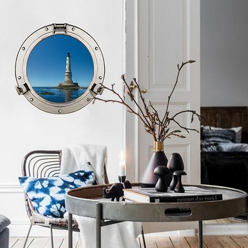 Décoration marine dans une joli salon tendance avec une fausse fenêtre ronde de hublot de bateau avec vue sur un phare marin.