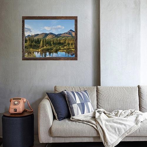 Joli salon de montagne personnalisé avec une fausse fenêtre adhésive en trompe-l'oeil offrant la vue sur un paysage de Chicoutimi au Canada.
