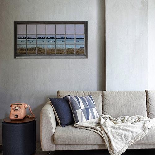 Adhésif mural fenêtre avec une vue sur des flamands roses, mis en ambiance sur un mur clair