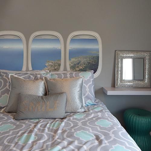 Sticker Vue du Ciel pour tête de lit sur mur gris au-dessus d'un lit gris et turquoise