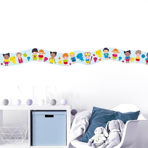 Sticker frise enfants du monde dans chambre d'enfant avec coussin bleu et peluches