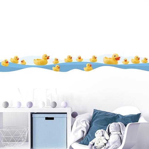 Sticker frise canards en pastique au bord de l'eau dans chambre d'enfant avec coussin bleu et peluches