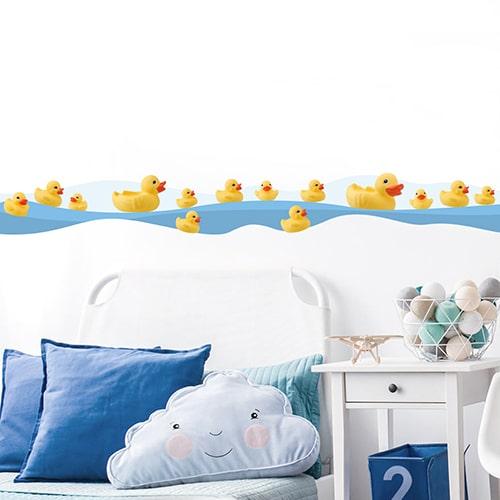 Sticker frise canards en pastique au bord de l'eau dans chambre d'enfant avec coussins bleus
