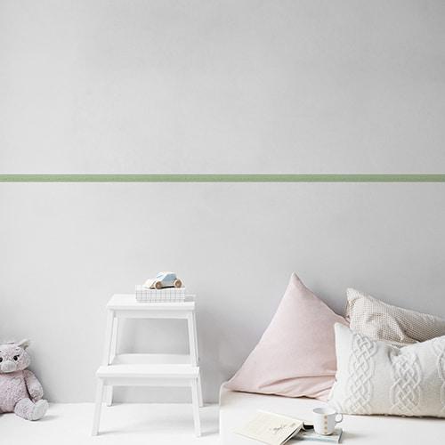 Sticker frise design vert sur mur clair avec coussins clairs