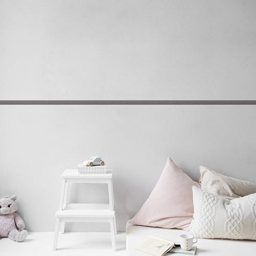 Sticker frise design bleu et gris sur mur clair avec coussins clairs