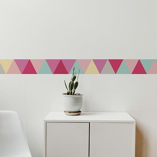 Sticker triangles rose turquoise gris et jaune sur mur blanc