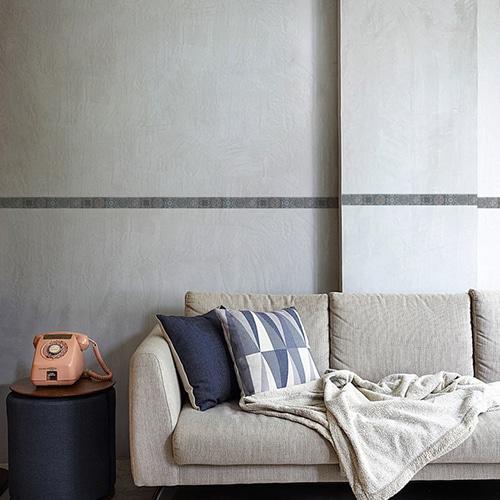 Frise carreaux de ciment adhésive imitation carrelage bleu et blanc au-dessus d'un canapé