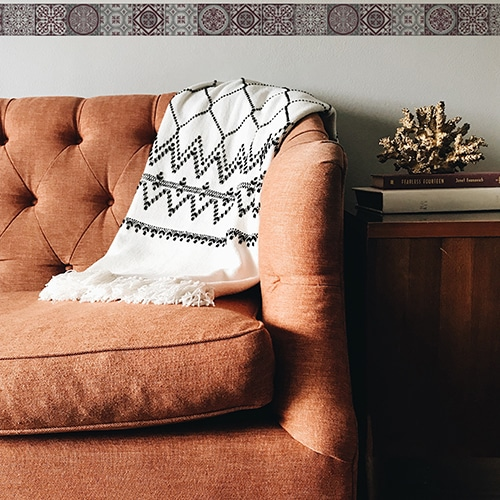 Frise imitation carrelage rouge et gris au-dessus d'un canapé