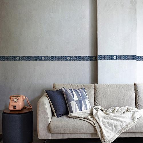 Sticker frise imitation carrelage design bleu au-dessus d'un canapé gris sur mur gris