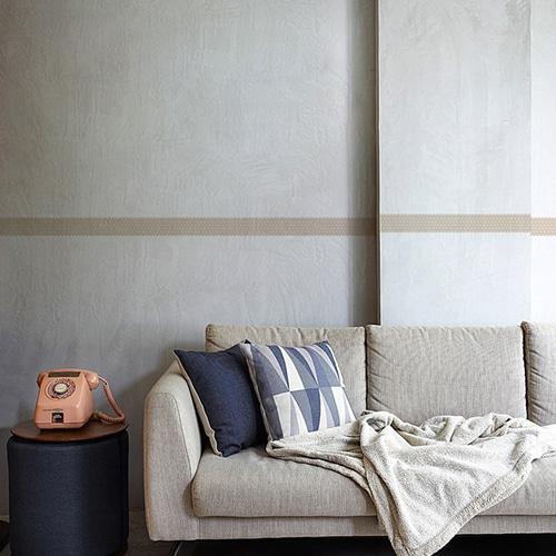 Sticker frise beige et points blancs au-dessus d'un canapé gris sur mur gris