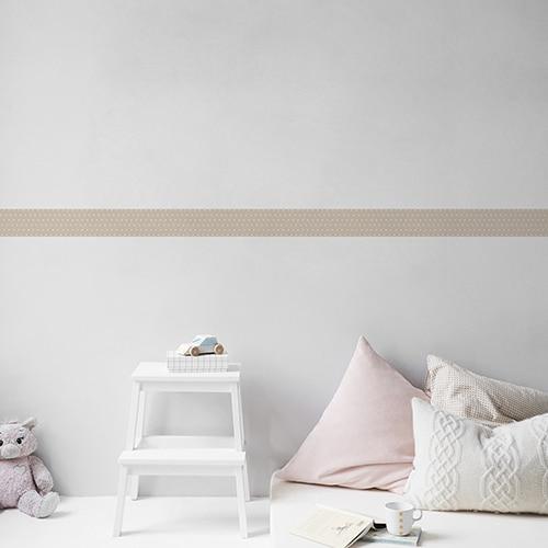 Sticker frise beige et points blancs sur mur clair avec coussins clairs