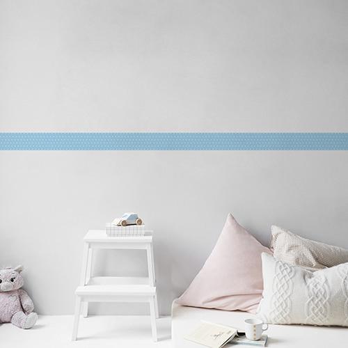 Sticker frise bleu et points blancs avec coussins clairs sur mur clair