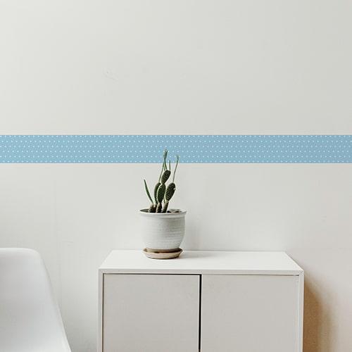 Sticker frise bleu et points blancs avec cactus décoratif sur mur blanc