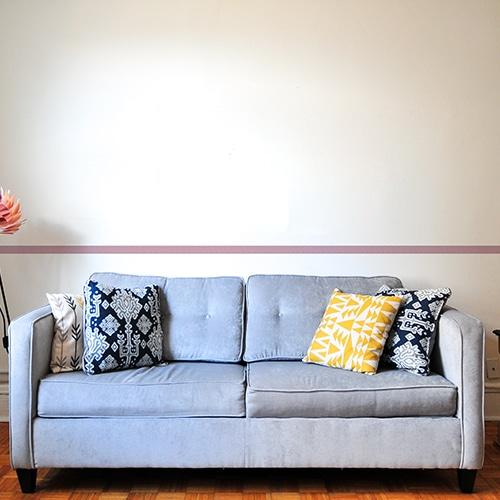 Sticker frise rose et points blancs au-dessus d'un canapé bleu