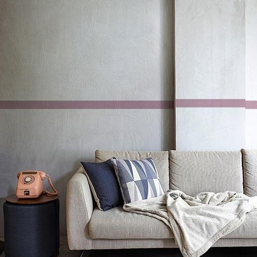 Sticker frise rose et points blancs au-dessus d'un canapé gris