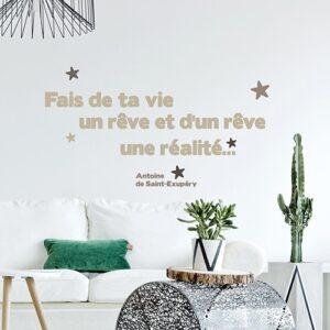 """Sticker citation - Phrase de Saint-Exupéry au-dessus d'un canapé blanc - """"Fais de ta vie un rêve et d'un rêve une réalité"""""""