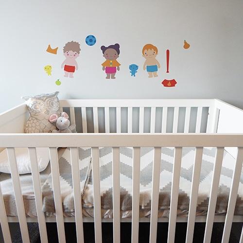 Stickers adhésifs poupées mis au-dessus d'un lit d'enfant.