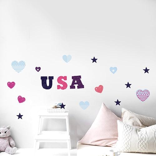 Sticker coeur rose et bleu et lettres USA collé au mur d'une chambre