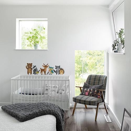 Stickers Animaux des bois dans chambre d'enfant sur mur blanc au-dessus d'un lit de bébé