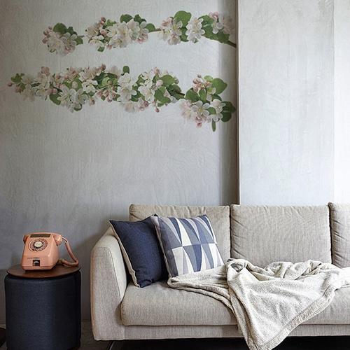 Sticker adhésif branche de pommier fleuri au-dessus d'un canapé gris