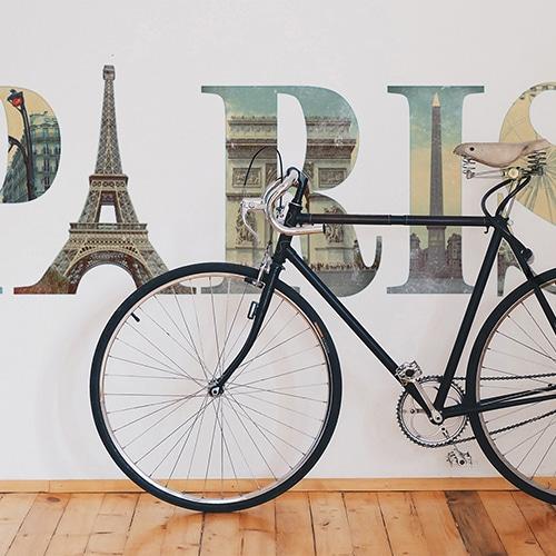 Autocollant mural écritures Paris avec motifs monuments de la ville mis en ambiance sur un mur blanc et derrière un vélo parisien premier plan