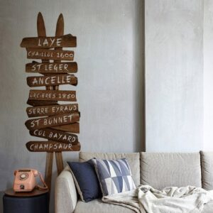 Salon vintage décoré avec un panneau de signalisation stations de ski en trompe-l'oeil fait avec des skis anciens en bois.