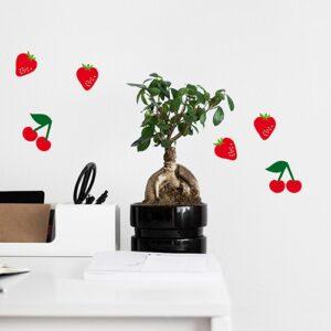 Stickers muraux adhésifs fraises et cerises sur un mur blanc