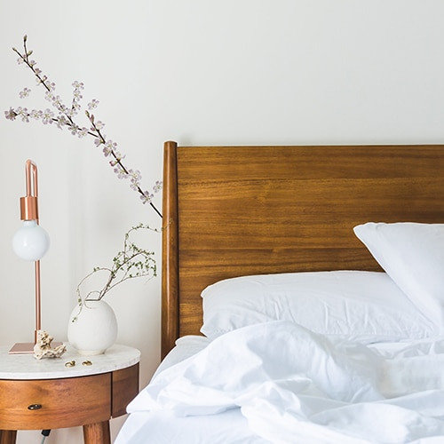 tickers Branches d'arbres en fleurs au balcon dans une chambre derrière un lit
