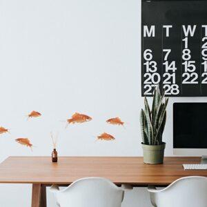 Sticker poissons rouges au-dessus d'une table avec plante décorative