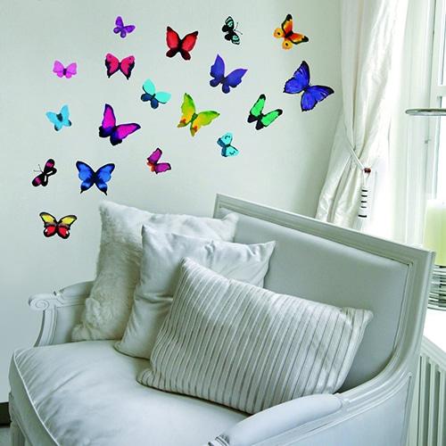 Stickers adhésif Papillons Fluos sur un mur blanc derrière un canapé blanc