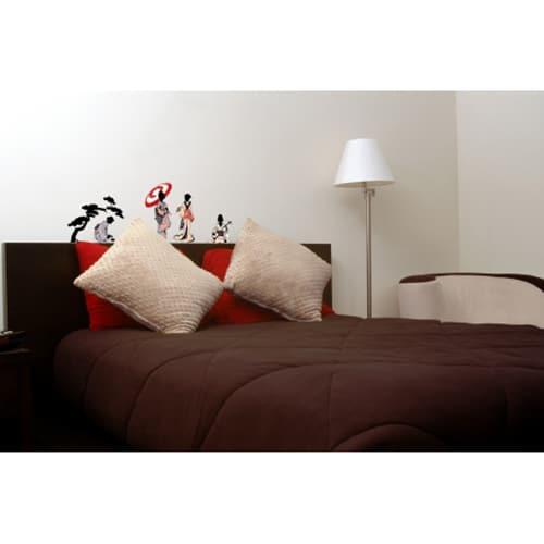 stickers muraux silhouettes japonaises mis en ambiance sur un mur blanc au dessus d'un lit