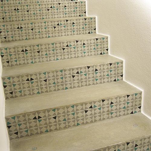 stickers autocollants petits triangles multicolores sur fond blanc pour contremarches, mis en ambiance sur des escaliers en bois gris clair
