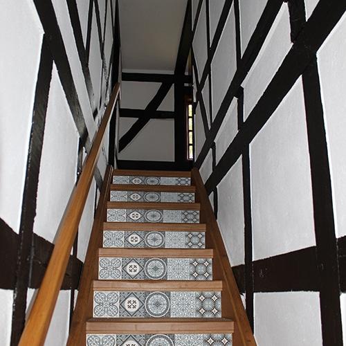 planche de stickers adhésifs style mosaïque bleu clair, blanc et noir pour contremarches, mis en ambiance sur escaliers marrons foncés