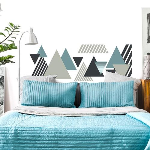 Sticker pour tête de lit Triangles Colorés sur mur blanc au-dessus d'un lit bleu