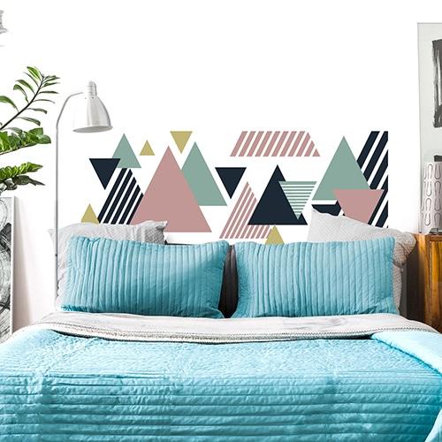 Sticker pour tête de lit Triangles Multicolores sur mur blanc au-dessus d'un lit bleu