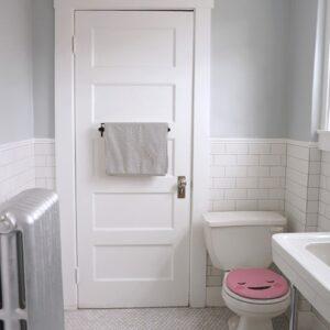 Sticker Smiley rose touchant collé sur des WC